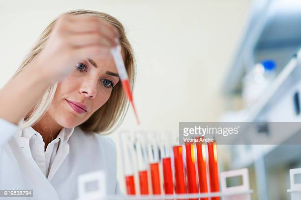 woman scientist working in laboratory - red tube stock pictures, royalty-free photos & images