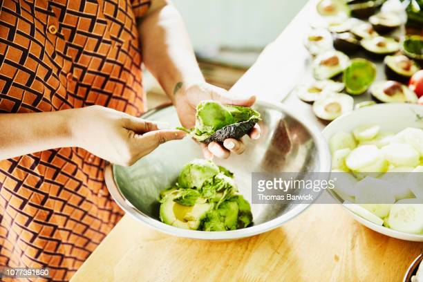 woman scooping avocado into bowl while preparing food for party in kitchen - avocado stock pictures, royalty-free photos & images