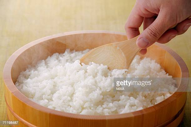 A woman scooping steamed rice