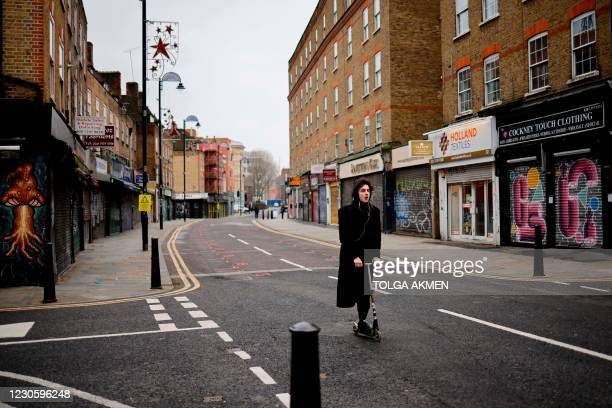 Woman scooters past shuttered shops along a deserted street in the City of London on January 15 during the third coronavirus lockdown. - Britain's...