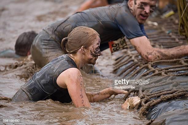 Woman scrambling out of muddy water