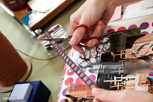Woman scrapbooking, cutting trim and arranging photos. Craft, hobby.