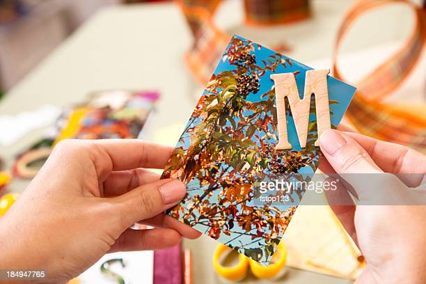 Woman scrapbooking, letter M on photograph. Art, craft, hobby.