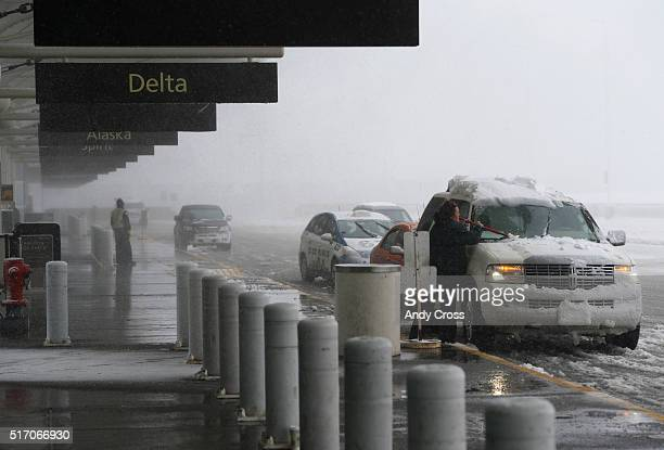 A woman scrapes off her windshield during a blizzard at Denver International Airport March 23 2016