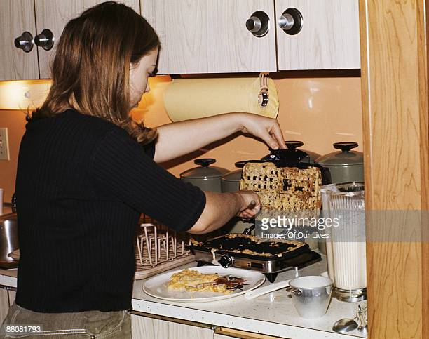 Woman scraping batter off waffle iron