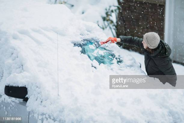 woman scraping snow and ice off car windshield - mitten stock pictures, royalty-free photos & images