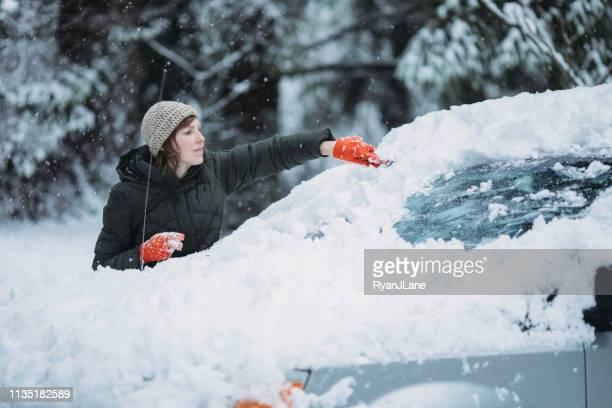 woman scraping snow and ice off car windshield - scraping stock photos and pictures