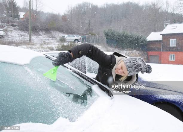 woman scraping snow from car in france - scraping stock photos and pictures