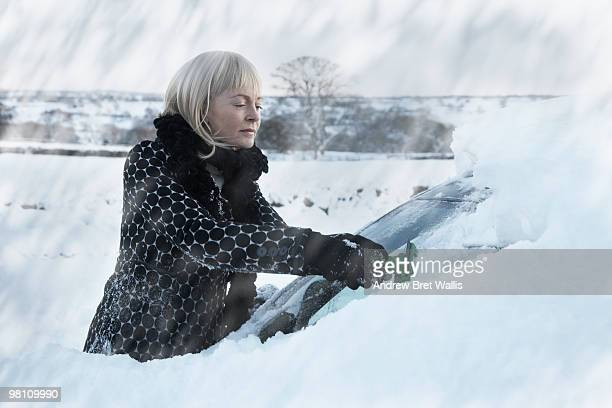 woman scraping snow off a car windscreen
