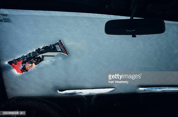 woman scraping snow off windshield, viewed from inside car - scraping stock photos and pictures