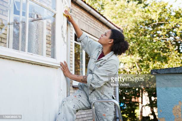 woman scraping wall during home renovation - renovation stock pictures, royalty-free photos & images