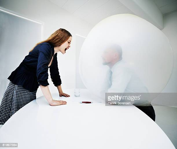 Woman screaming at a man inside a balloon
