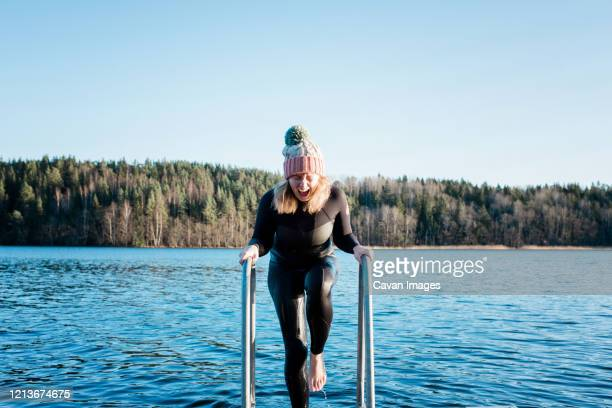 woman screaming from swimming in the cold water in the sea in winter - cold temperature stock pictures, royalty-free photos & images