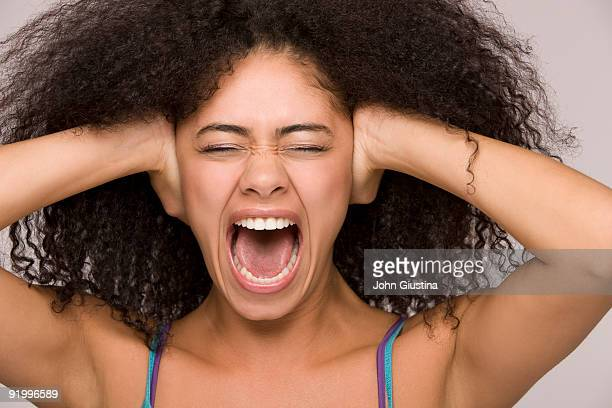 Woman screaming, hands over her ears, eyes closed.