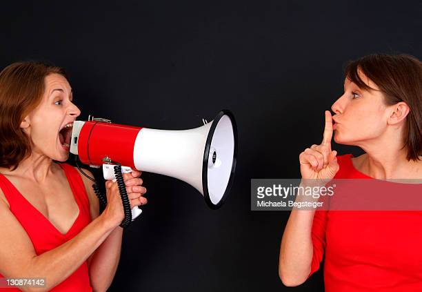 woman screaming in megaphone, other woman wants her to quiet down