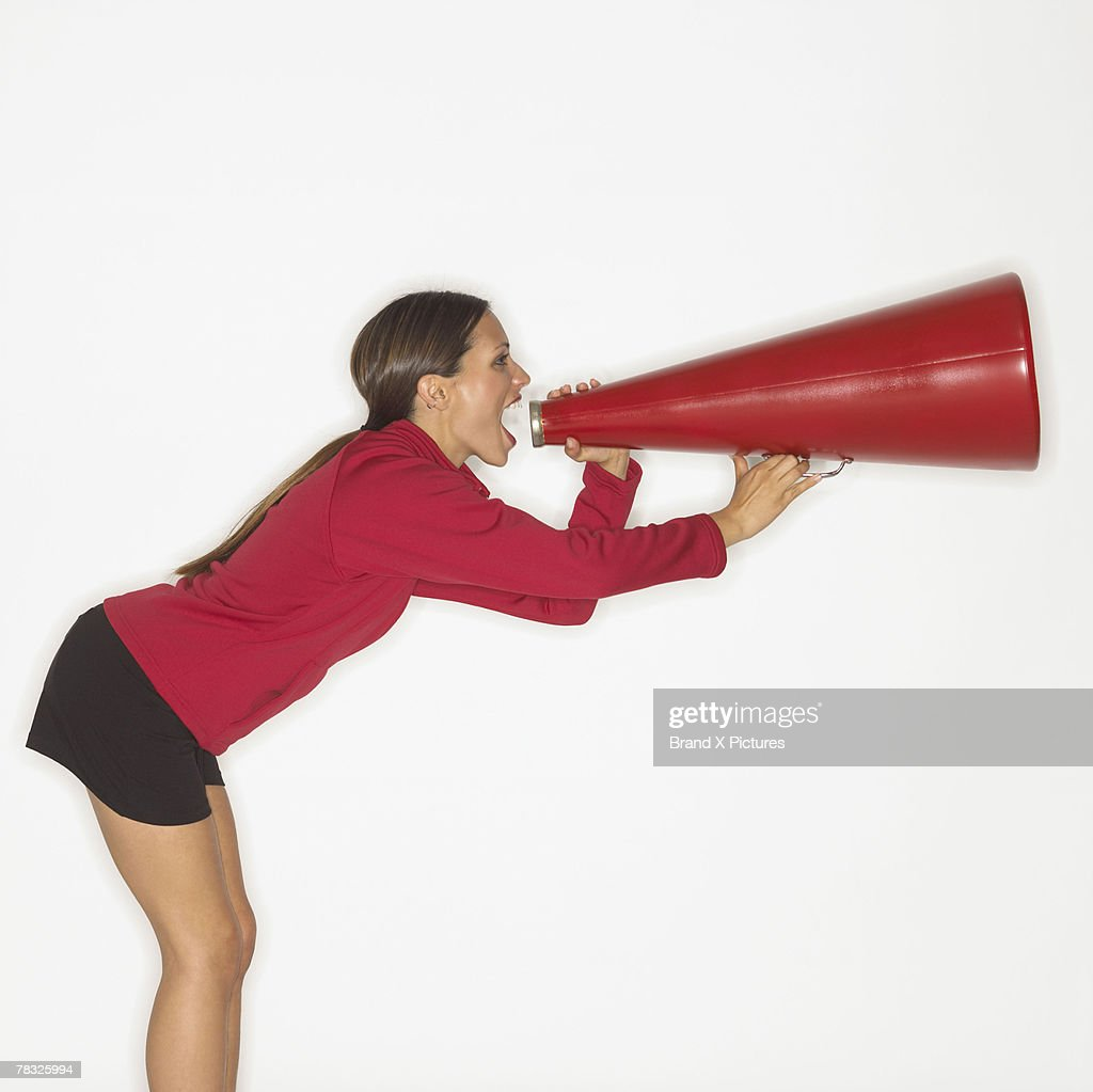 Woman screaming into bullhorn : Stock Photo