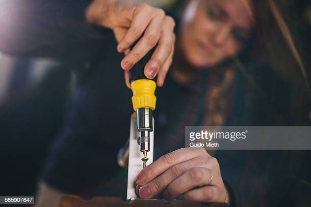 Woman screwing a holder on a wood board