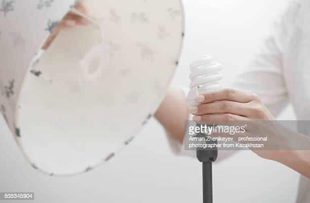 Woman screwing energy saving lamp