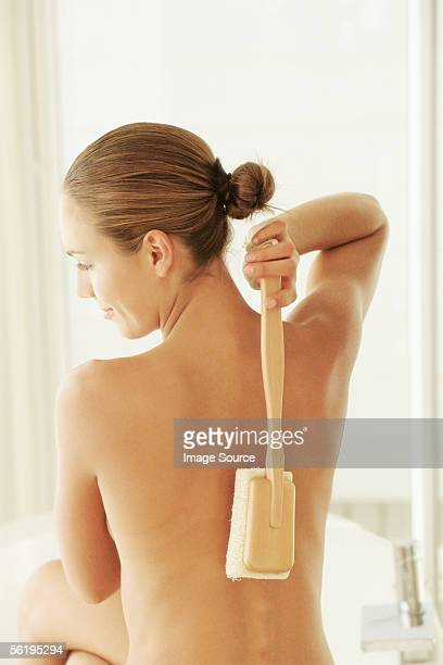 woman scrubbing back - loofah stock photos and pictures