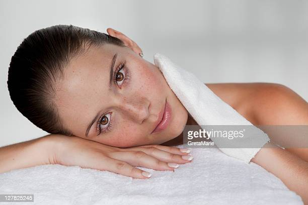Woman scrubbing her face with cloth