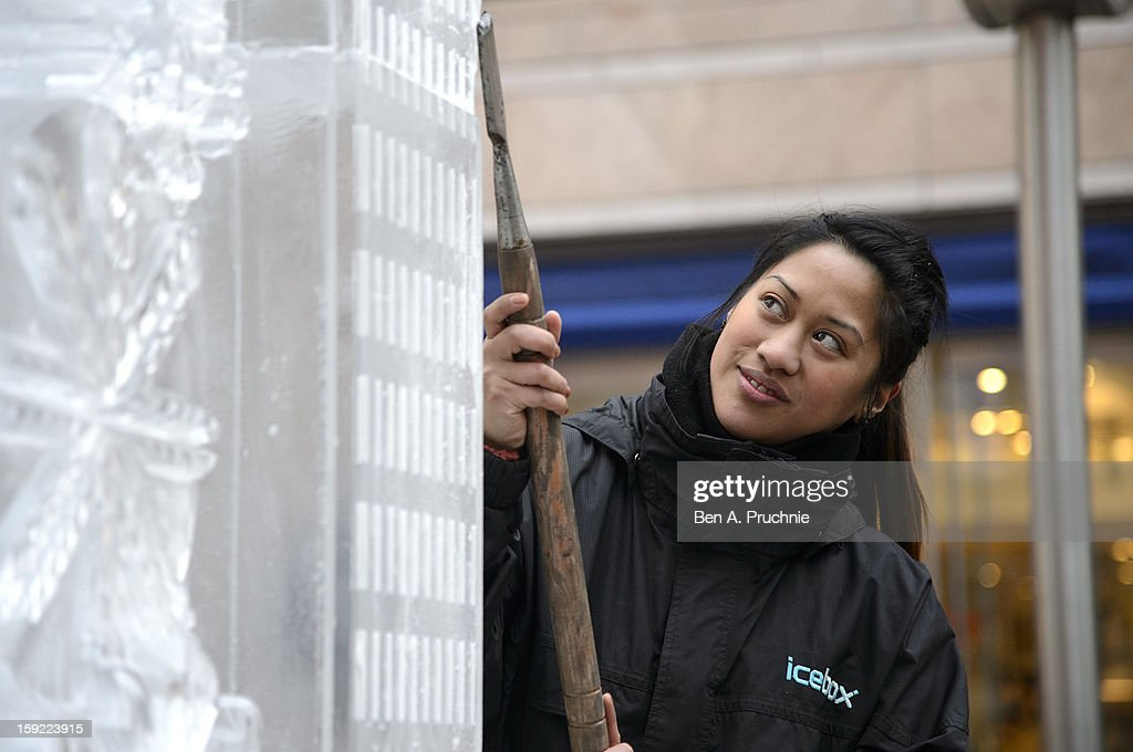 A woman sculpts an ice Canary Wharf as the London Ice Sculpting festival is launched on January 10, 2013 in London, England.