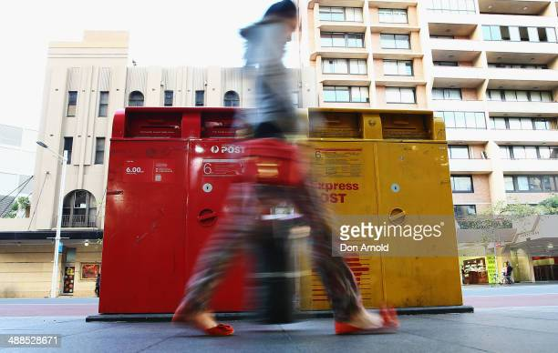 A woman scuttles past a Post Office Box outside the Darlinghurst Post Office on May 7 2014 in Sydney Australia Australia Post is considering a...