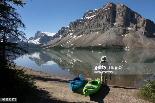 Woman sea kayak Bow Lake reflections Banff National Park Alberta Canada glacier