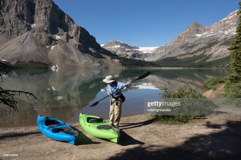 Woman sea kayak Bow Lake reflections Banff National Park Alberta Canada glacier : Stock Photo