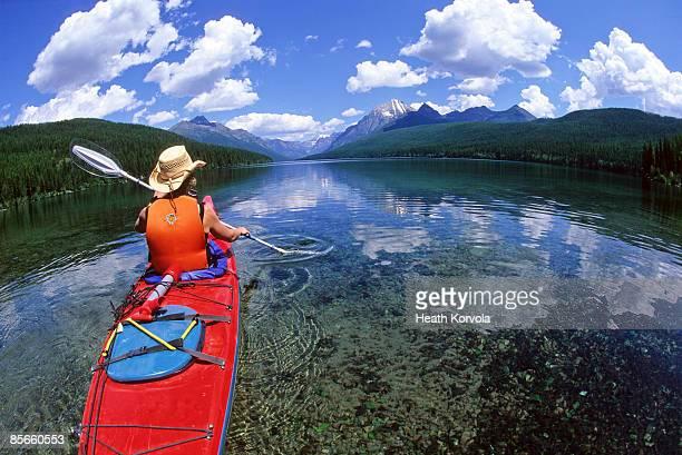 woman sea kayaking on pristine lake. - montana - fotografias e filmes do acervo