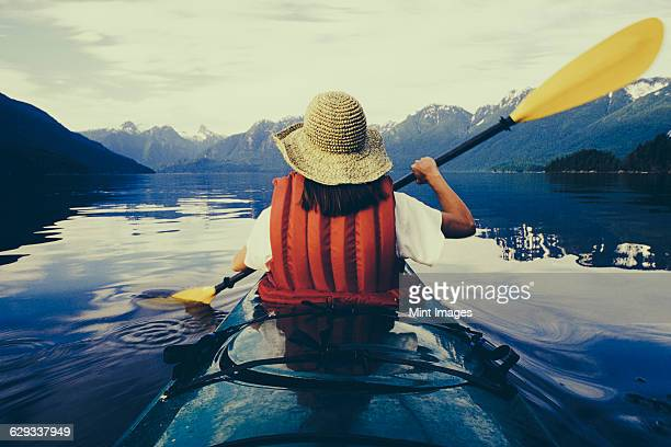 A woman sea kayaking on the flat calm water of Muir Inlet in Glacier Bay National Park.