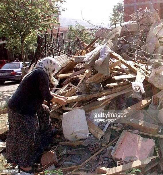 A woman searches 18 August 1999 the wreck of a house in a suburb of the town of Izmit 150 kms east of Istanbul on the Marmara Sea where the death...