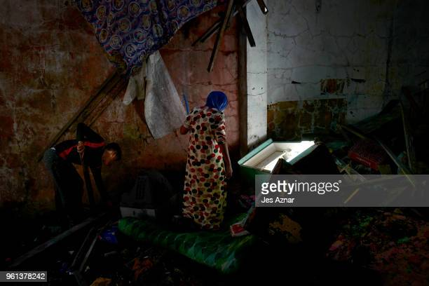 A woman searches a dark corner of their destroyed house to look for anything that can still be useful on May 10 2018 in Marawi Philippines Kairam and...