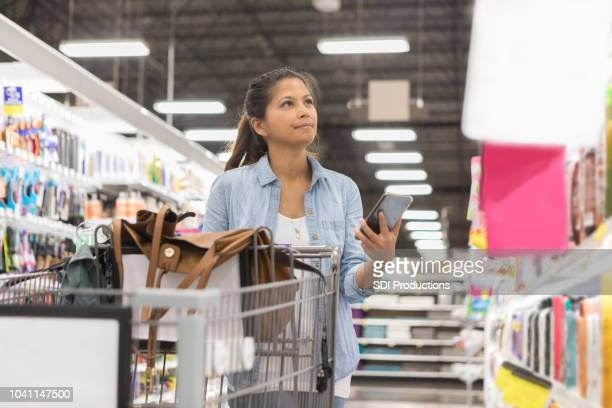 woman searches supermarket for item on list - household equipment stock pictures, royalty-free photos & images