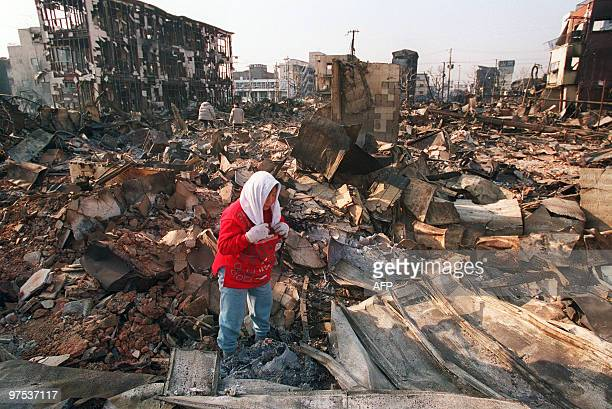 A woman searches through the ashes of what once was her community 21 January 1995 in the Nagata area of Kobe Nearly twosquare blocks burnt to the...
