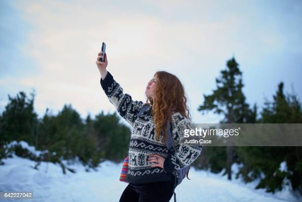 woman searching a signal with her mobile phone in snowy forest