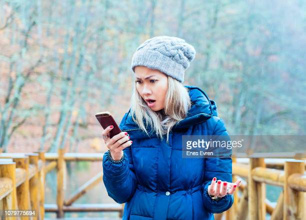 woman searching for a mobile network in woods - no signal - inconvenience stock pictures, royalty-free photos & images