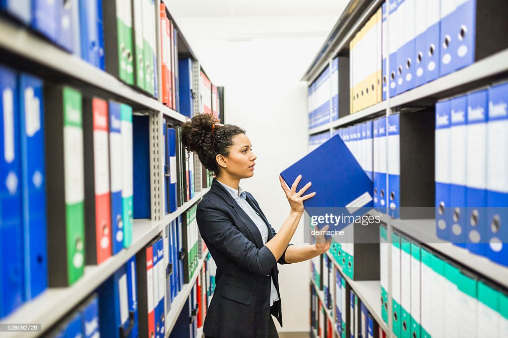Woman searching for files in paper archive : Stock Photo