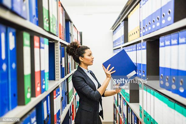 Woman searching for files in paper archive