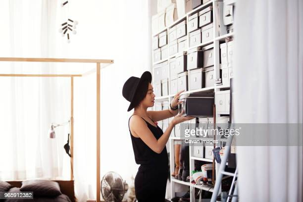 woman searching in box by shelves in bedroom - arrangement stock pictures, royalty-free photos & images