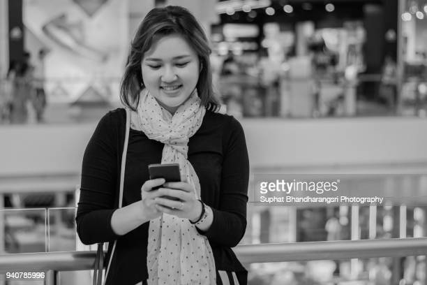 Woman searching smartphone in shopping mall
