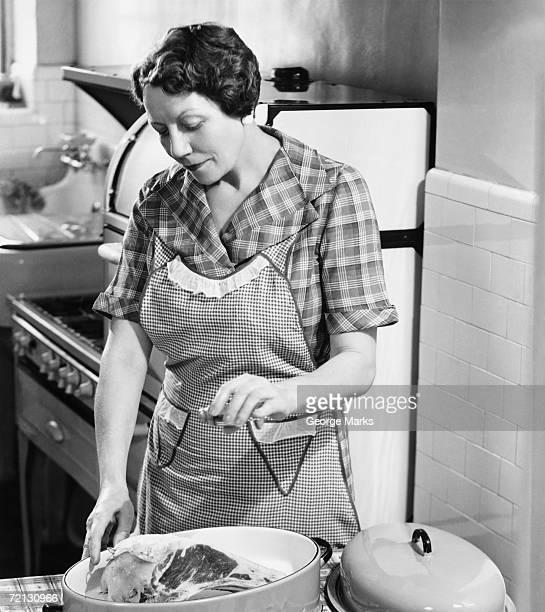 Woman seasoning meat in roasting dish (B&W)