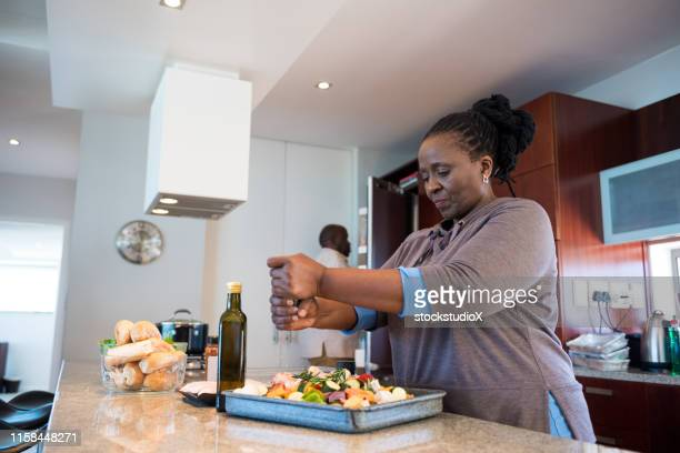woman seasoning salad while preparing food at home - 50 59 years stock pictures, royalty-free photos & images