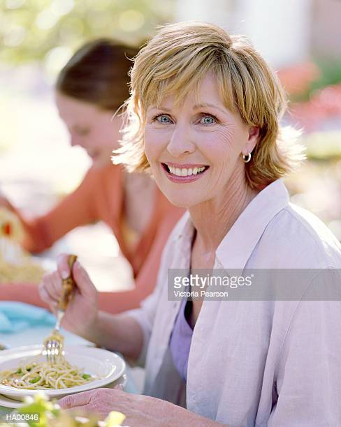 woman seated at outside table eating pasta, portrait - mid length hair stock pictures, royalty-free photos & images