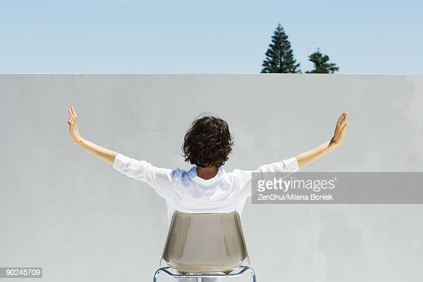 Woman seated facing wall, arms outstretched, rear view