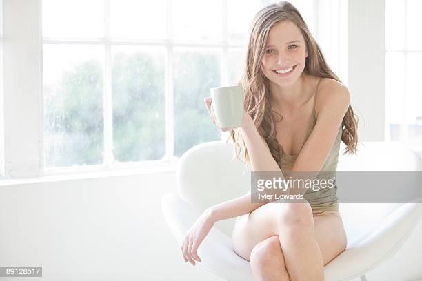 Woman seated holding mug smiling