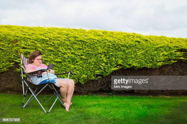 woman seated in a camping chair in a sheltered spot by a hedge, using a digital tablet. - cadeira dobrável - fotografias e filmes do acervo