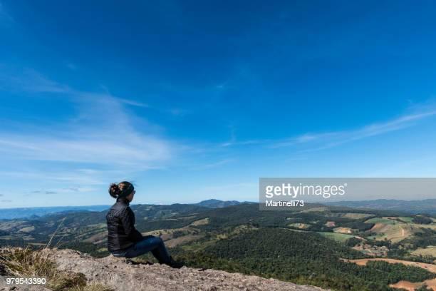女性グアディアナ山の岩に座っての冬の日、ゴンサルベス、丘をミナスジェ ライス州 - ミナスジェライス州 ストックフォトと画像