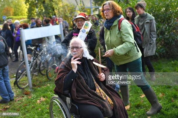 A woman seated in a wheelchair and wearing a Bigouden headdress smokes a rollup cigarette as she takes part in a march organised by opponents to a...