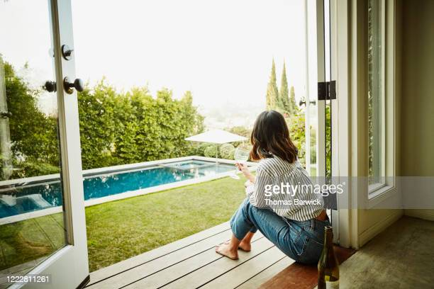 woman seated in doorway of home looking out over pool in backyard - alcohol stock pictures, royalty-free photos & images