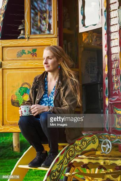 A woman seated on the steps of a caravan, holding a mug of tea.